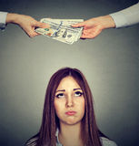 Worried sad woman looking up at two hands exchanging money. Upset worried sad woman looking up at two hands exchanging money royalty free stock images