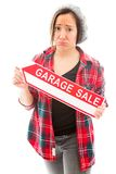 Worried saleswoman holding a garage sale sign. Young adult caucasian woman isolated on a white background Stock Images