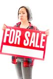 Worried saleswoman showing a for sale sign Royalty Free Stock Images