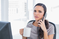 Worried secretary answering phone. In her office Stock Photography