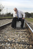 Worried senior businessman sits on suitcase on railroad track. Defeated homeless senior businessman sits on suitcase on railroad train tracks pondering his Royalty Free Stock Photo