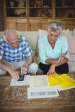 Worried senior couple checking bills in living room Royalty Free Stock Photos