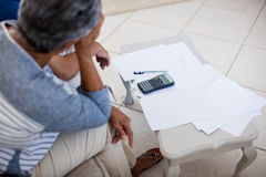 Worried senior couple checking bills in living room Royalty Free Stock Images