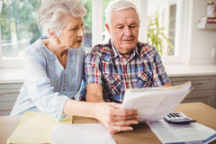 Worried senior couple checking their bills Royalty Free Stock Images
