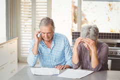Worried senior couple with documents in kitchen stock photography