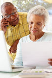 Worried Senior Couple Using Laptop At Home Stock Photos
