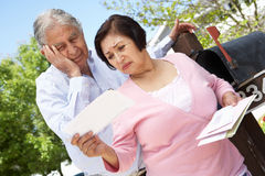 Worried Senior Hispanic Couple Checking Mailbox Royalty Free Stock Photography