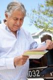 Worried Senior Hispanic Man Checking Mailbox Stock Photo