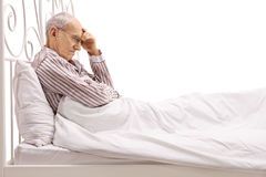 Worried senior lying in bed Stock Photography