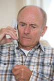Worried Senior Man Answering Telephone At Home Stock Photo