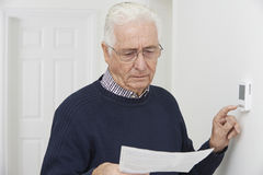 Worried Senior Man With Bill Turning Down Central Heating Thermo. Concerned Senior Man With Bill Turning Down Central Heating Thermostat Royalty Free Stock Photo