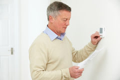 Worried Senior Man With Bill Turning Down Heating Thermostat. Worried Senior Man With Bill Turns Down Heating Thermostat Royalty Free Stock Image