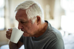 Worried senior man having black coffee in the bedroom. At home Stock Photography
