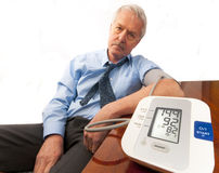 Worried senior man with high blood pressure. Worried and stressed senior man in shirt and tie (businessman or teacher) showing a high blood pressure reading on Stock Photos