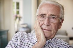 Worried senior man at home looking to camera, close up stock photography