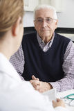Worried Senior Man Meeting With Doctor In Surgery Stock Photo