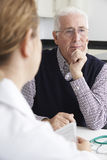 Worried Senior Man Meeting With Doctor In Surgery Stock Images