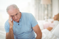 Worried senior man sitting in bedroom. Worried senior men sitting in bedroom at home Royalty Free Stock Photography