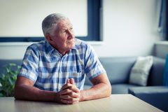 Worried senior man sitting in living room Stock Photography