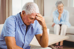Worried senior man sitting on sofa Stock Photos