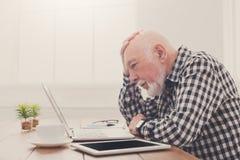 Worried senior man using laptop at home Stock Photography