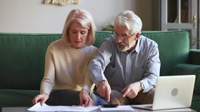 Worried old couple stressed about unpaid bank debt holding bills