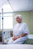 Worried senior patient sitting on bed royalty free stock photo