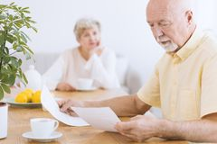Senior analyzing financial papers. A worried senior sitting at a table and analyzing financial papers and his wife looking at him Royalty Free Stock Images