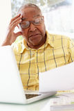 Worried Senior Studying Paperwork At Home Stock Images