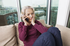 Worried senior woman answering smart phone on sofa at home Stock Photography