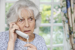 Worried Senior Woman Answering Telephone At Home Stock Images