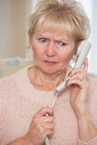 Worried Senior Woman Answering Telephone At Home Royalty Free Stock Photos