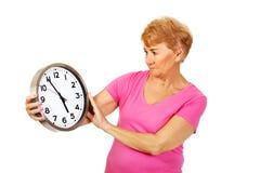 Worried senior woman holding big clock Stock Photo