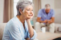 Worried senior woman sitting on sofa Royalty Free Stock Images