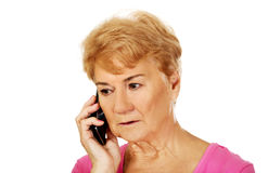 Worried senior woman talking through phone Stock Image