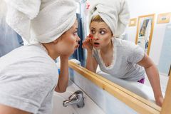 Woman looking at her reflection in mirror Stock Photo
