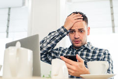 Worried shoked man looking on laptop at cafe Stock Photos
