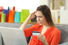 Worried shopper buying online with credit card. Sitting on a couch in the living room at home Royalty Free Stock Photo