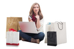 Worried shopping woman holding card and thinking Stock Photo