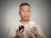 Worried skeptical surprised man reading bad news sms on smartphone Royalty Free Stock Image