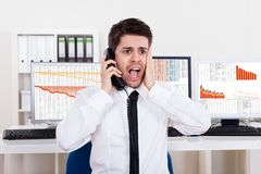 Worried stock broker on the phone. Worried stock broker talking on the phone backed by graphs depicting a crisis and a bear market with huge losses in the market Stock Photos