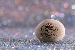 The worried stone emoji. Emotions on color glitter boke background royalty free stock photo