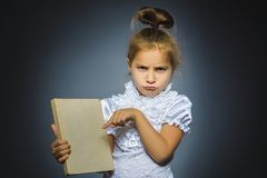 Worried or stressed girl with book. child on grey background. studies concept royalty free stock image