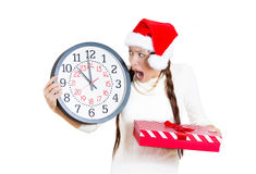 Worried, stressed, in a hurry young woman wearing red santa claus hat, holding clock Royalty Free Stock Photography