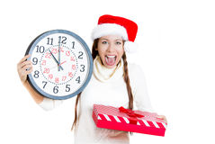 Worried, stressed, in a hurry young woman wearing red santa claus hat, holding clock Royalty Free Stock Photos