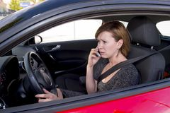 Worried and stressed woman driving car while talking on the mobile phone distracted Royalty Free Stock Photography