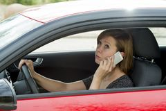 Worried and stressed woman driving car while talking on the mobile phone distracted Royalty Free Stock Photos