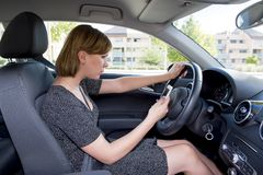 Worried and stressed woman driving car while texting on mobile phone distracted. Young woman worried and stressed driving car while texting with mobile phone royalty free stock photography