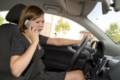 Worried and stressed woman driving car while texting on mobile phone distracted Royalty Free Stock Photos
