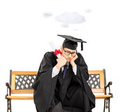Worried student on bench holding diploma and a cloud floating ov Stock Photos